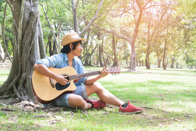 asian-man-playing-guitar-in-the-park_1428-994.jpg