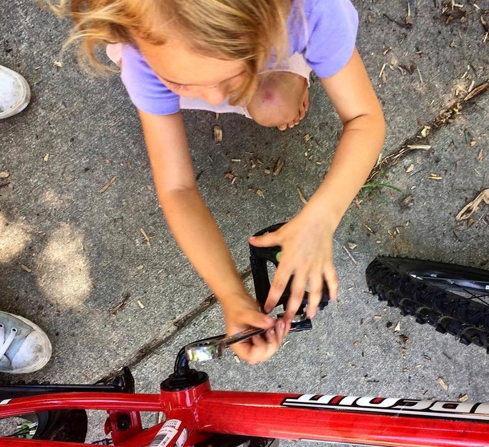 Young girls from Trips for Kids Charlotte works on her bike pedals.