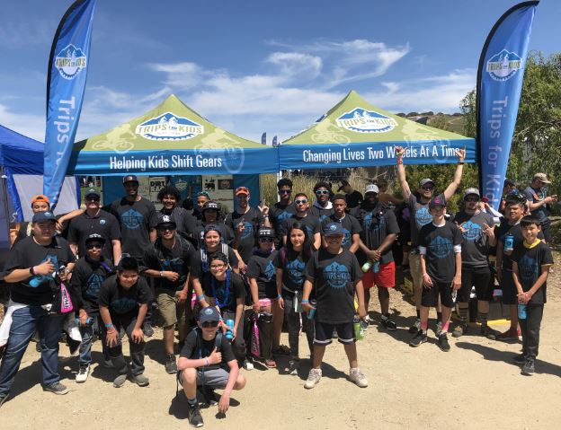 Youth from multiple chapters pose in front of our Trips for Kids booth at the 2019 Sea Otter Classic.
