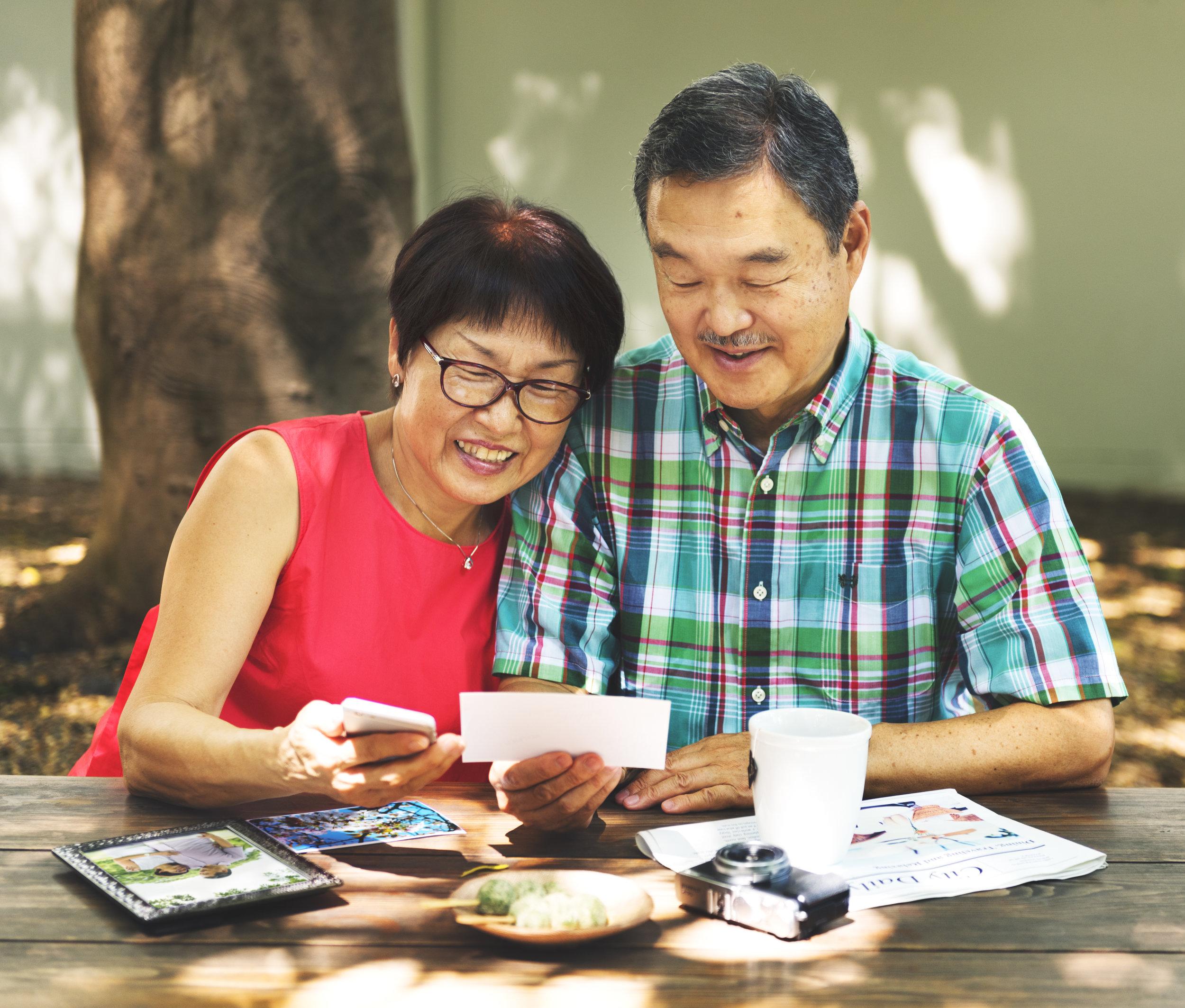 asian-senior-couple-reminiscing-photos-concept-PPFGC66.jpg