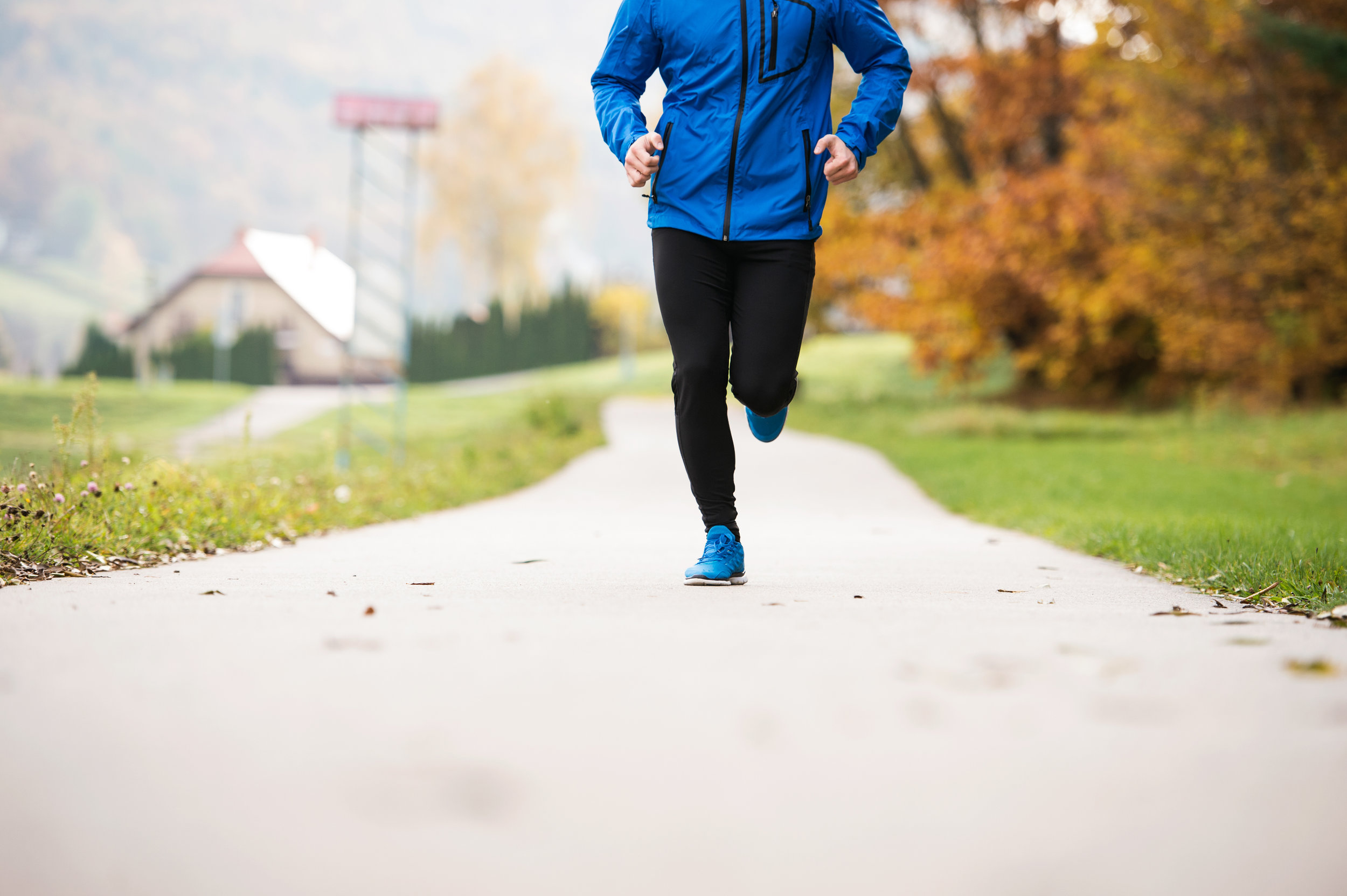 graphicstock-unrecognizable-young-athlete-in-blue-jacket-running-outside-in-colorful-sunny-autumn-nature-on-an-asphalt-path-leading-through-green-grass-trail-runner-training-for-cross-country-running_rOgasQ2Szb.jpg