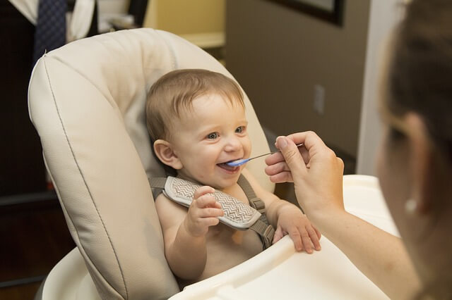 Happy baby being fed in highchair.jpg