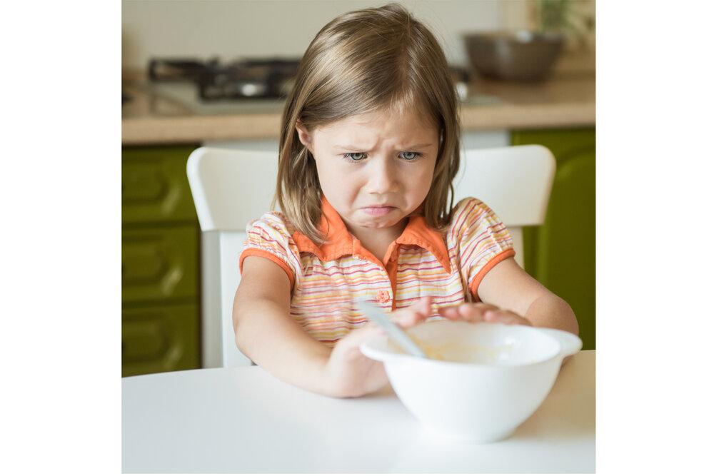 Unhappy girl pushing away bowl