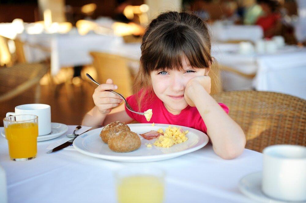 Young girl eating eggs