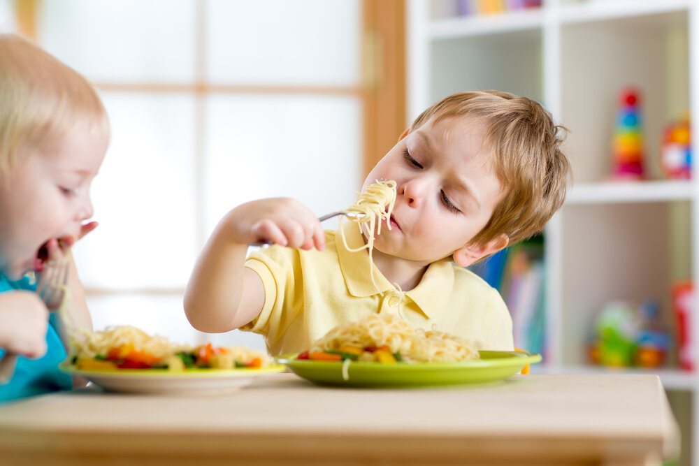 Toddler boys eating spaghetti with a fork