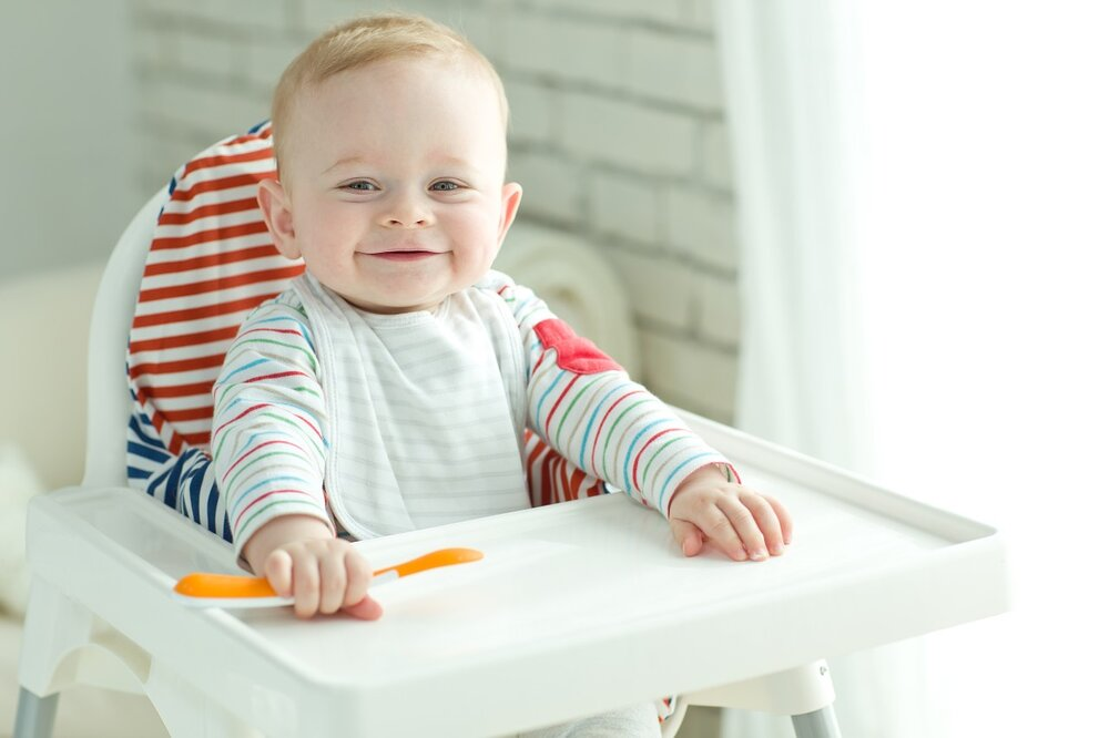 Baby boy sat in white highchair with orange baby spoon