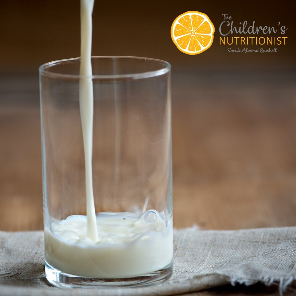 a glass tumbler with milk being poured into it