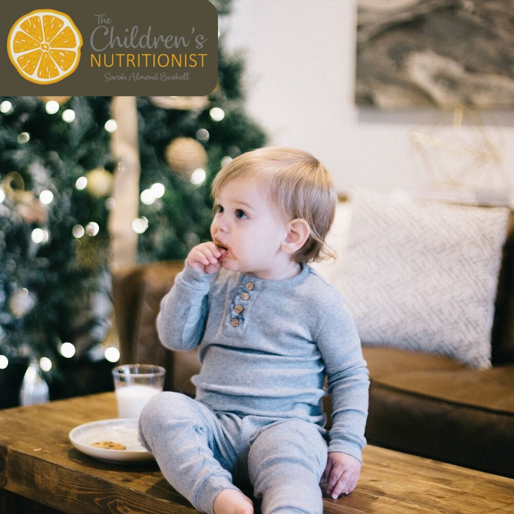 a toddler sat having cookies and milk with a christmas tree in the background