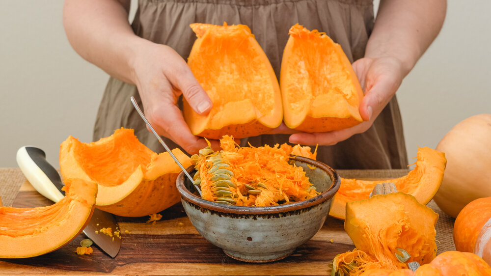 woman holding cut up chunks of pumpkin with seeds in a bowl