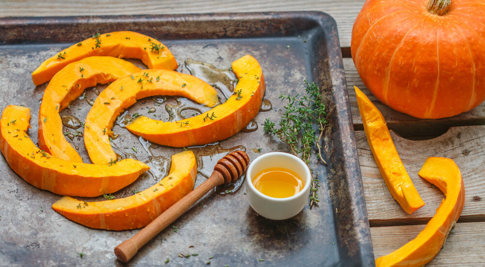 slices of pumpkin on a baking tray sprinkled with herbs