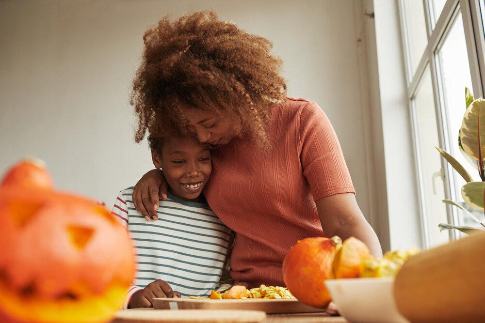 mother hugging her daughter and carving pumpkin together