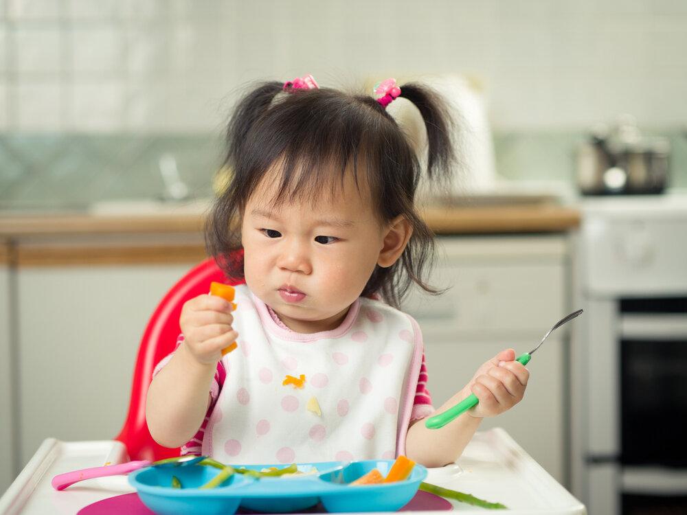 asian baby girl eating carrot
