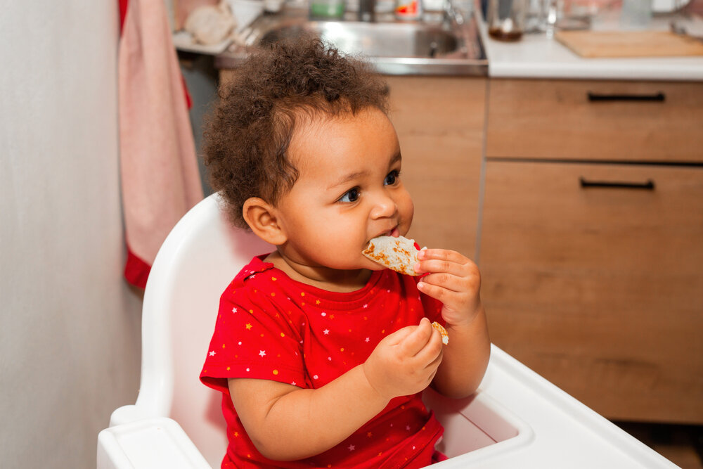 african baby girl eating pizza