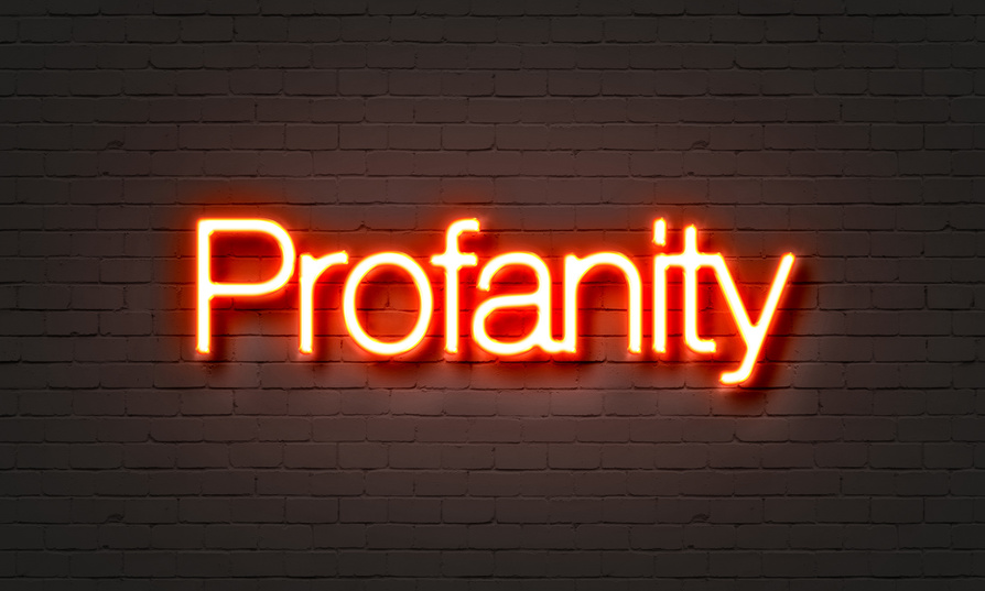 Profanity neon sign on brick wall background.