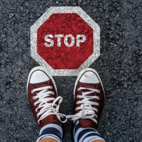 Stop man legs in sneakers standing on asphalt road and stop sign