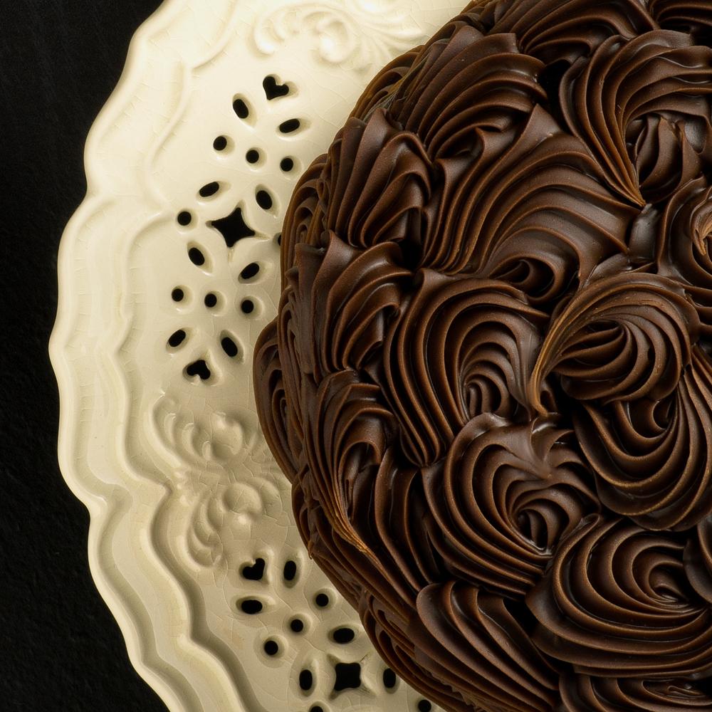 swirly chocolate frosting on cake