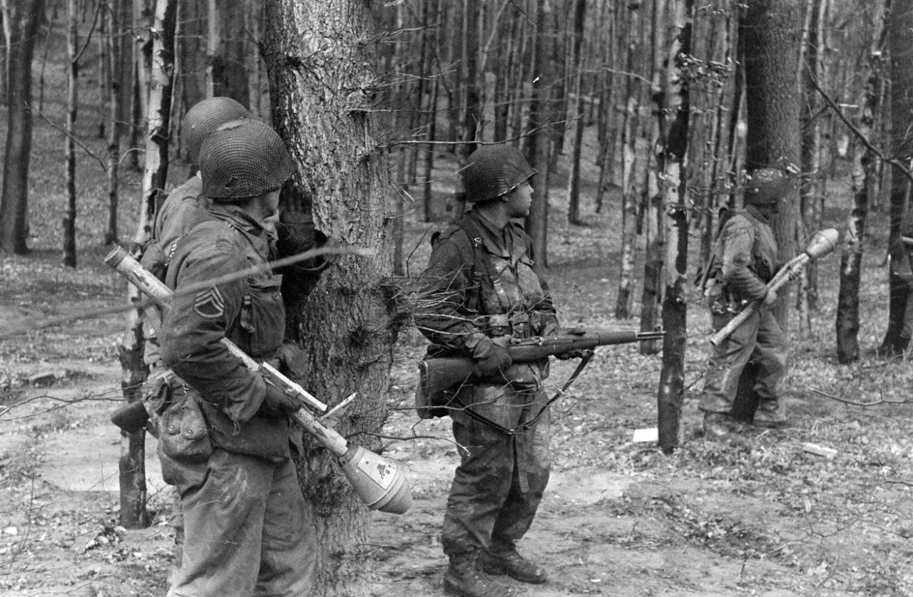 2nd Armored Division infantrymen with captured German Panzerfausts searching the woods in the vicinity of Lemgo, Germany, 1945.