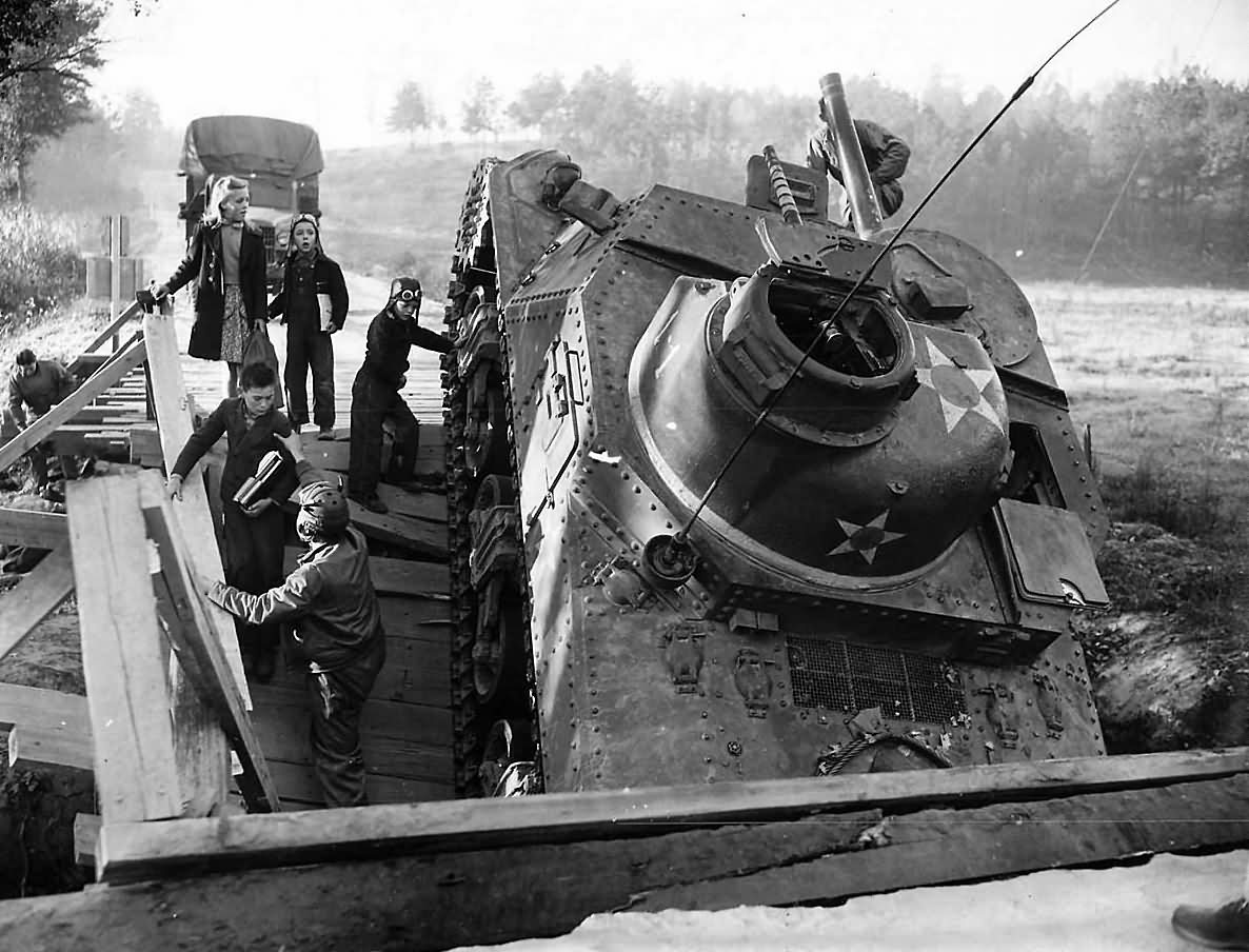 During a pre-war training exercise this 2nd Armored Division M3 Lee collapsed the bridge. The crew failed to see the bridge weight limit while utilizing blackout drive. The crew is helping the local kids get across for school.