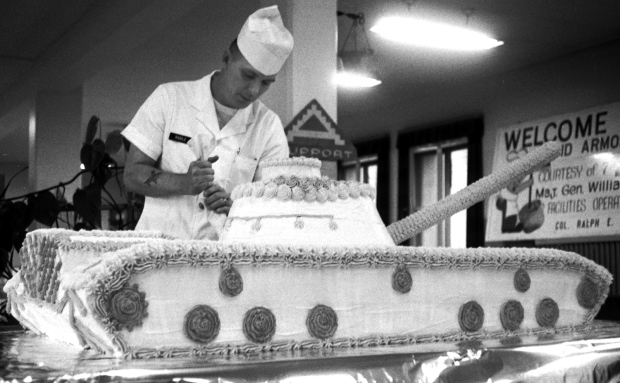 "Frankfurt, West Germany, October, 1963: Sgt. 1st Class Dawson Riddle of B Co., 14th Quartermaster Battalion, puts the finishing touches on a tank-shaped cake — weighing over 200 pounds — baked to welcome the first Operation Big Lift arrivals to Rhein-Main Air Base. In Big Lift, described as ""a historic demonstration of the United States' power to throw a quick fighting punch overseas,"" more than 200 air transports were bringing 16,000 2nd Armored Div. soldiers and supporting units to Germany for war games. Stars & Stripes photo"
