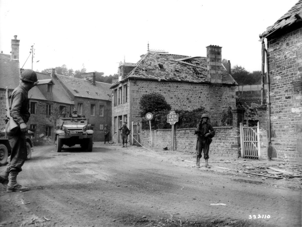 Infantry and a half-track of the 41st Armored Infantry Regiment enter the village of Lonlay L'Abbaye, France, 14th Aug 1944.