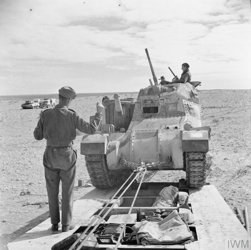 Men of the Royal Electrical and Mechanical Engineers guide a Grant tank onto a Scammell tank transporter to take it to a light repair workshop, 19 Jan 1943. IWM photo E 21405