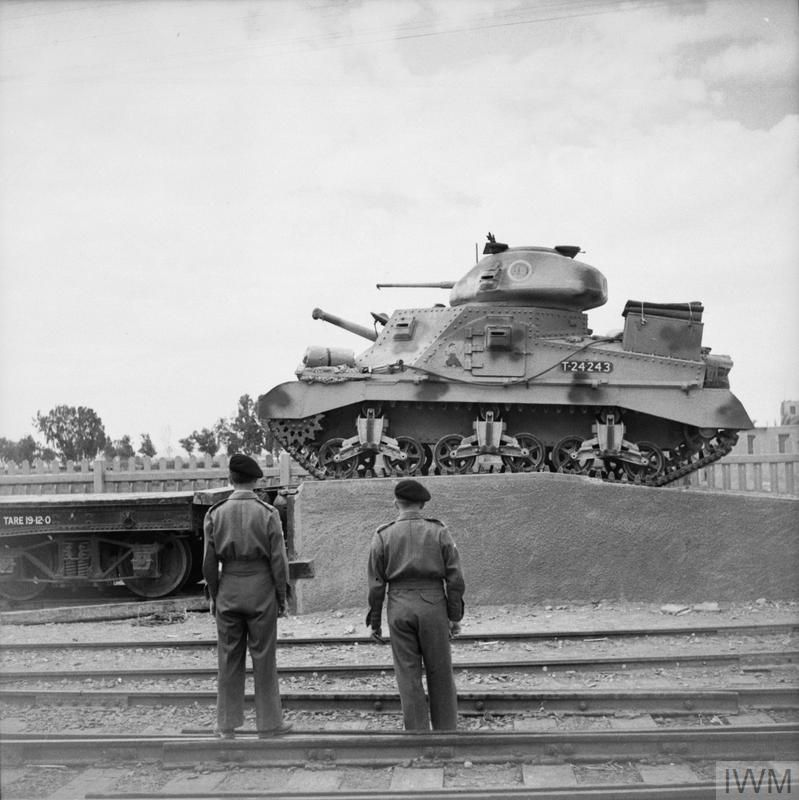 A Grant tank of 'C' Squadron HQ, 3rd Royal Tank Regiment, 7th Armoured Division, being loaded aboard a railway flatcar to be transported to the desert, 29 Mar 1942. IWM photo E 9915