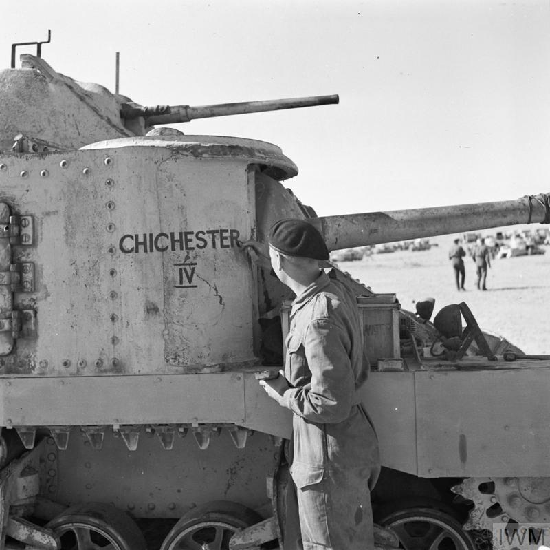 A soldier painting the name 'Chichester IV' onto the side of a Grant tank, 29 Mar 1942. IWM photo E 9892