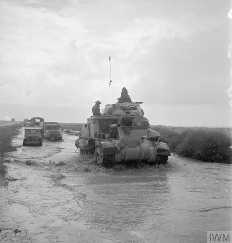 A Grant tank and trucks make their way along a road flooded by recent rains while in pursuit of the enemy, 10 Nov 1942. IWM photo E 19230