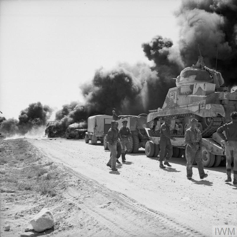The aftermath of an attack by Stukas on vehicles on the Gabes road east of El Hamma. Two lorries blaze after being hit, but the Grant tank on a transporter in the foreground was unscathed, 1 Apr 1943. IWM photo NA 1794