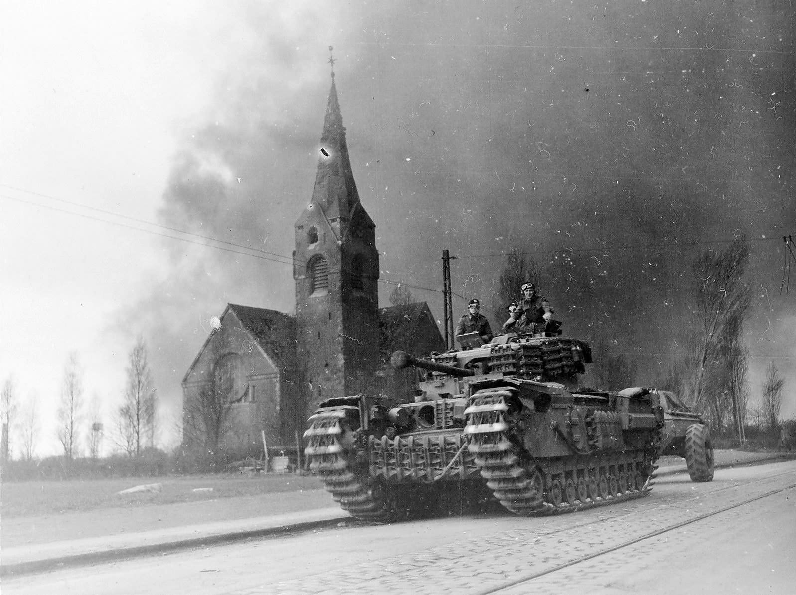 A Churchill Crocodile flamethrower tank of 31st Armoured Brigade, 79th Armoured Division, moves past a church at Oberhausen in the Ruhr, Germany, April 1945. Smoke from the burning Ruhrchemie AG synthetic oil plant (Sterkrade/Holten) fills the sky behind. IWM photo EA 60392.