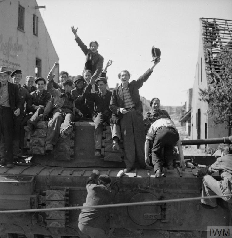 Former French and Dutch slave workers celebrate their liberation aboard a Churchill Crocodile tank of 7th Royal Tank Regiment in Bremen, 25 Apr 1945.IWM photo BU 4299.