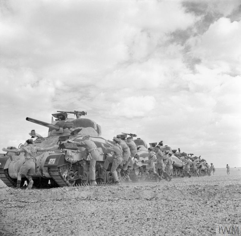 Crews climb aboard Sherman tanks of The Queen's Bays (2nd Dragoon Guards), 1st Armoured Division.El Alamein, 24 Oct 1942. IWM photo E 18376.