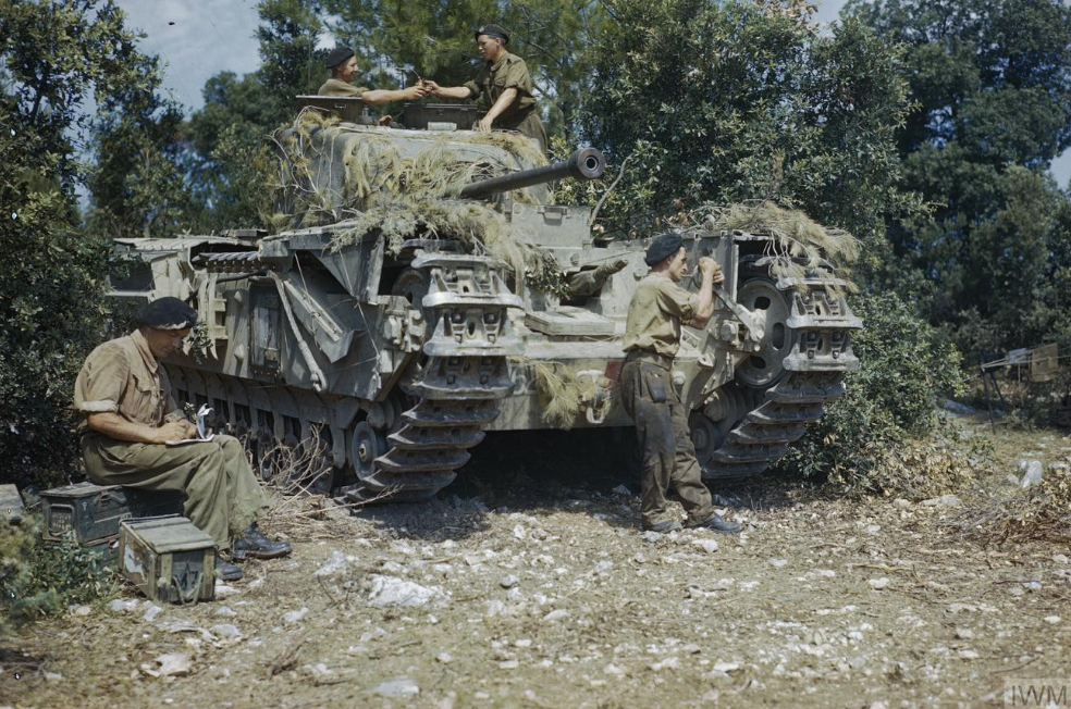 A Churchill tank, possibly of the 51st Royal Tank Regiment, is given a final check in a harbour area of Italy. IWM photo TR 2017.