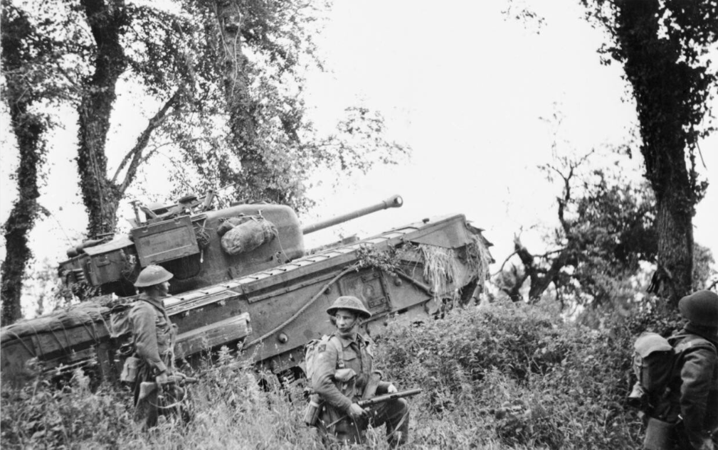 A Churchill tank of 7th Royal Tank Regiment, 31st Tank Brigade, supporting infantry of 8th Royal Scots during Operation 'Epsom', 28 Jun 1944. IMW photo B 6124.