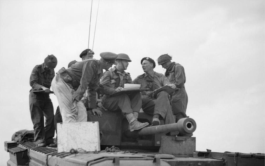 Tank and infantry officers confer on a Churchill tank of 7th Royal Tank Regiment, 31st Tank Brigade, during Operation 'Epsom', 28 Jun 1944. IMW photo B 6113.