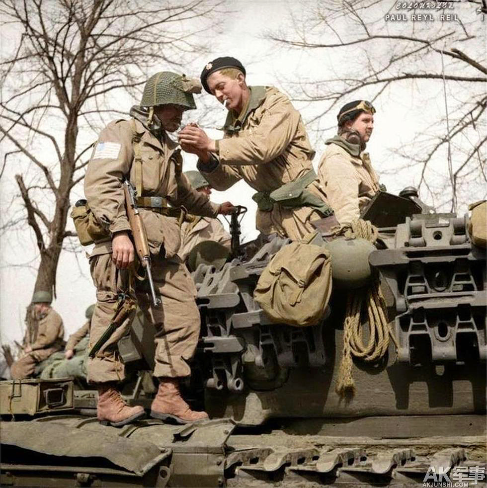 17th Airborne Division paratrooper gets a light from a Churchill tank crewman of 6th Guards Armoured Brigade near Dorsten in North Rhine-Westphalia, Germany, 29 Mar 1945.