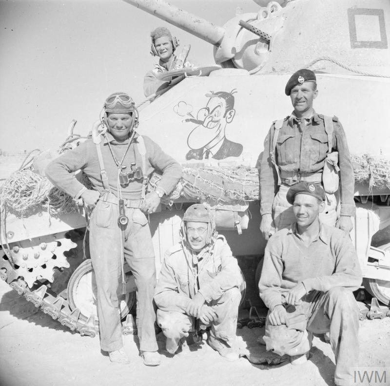 The crew of a Sherman tank pose beside their vehicle, decorated with a cartoon figure, during a break in fighting in the Western Desert, 29 Oct 1942. Note that three of the men are wearing American tank helmets, which were generally unpopular with British crews.IWM photo E 18696.