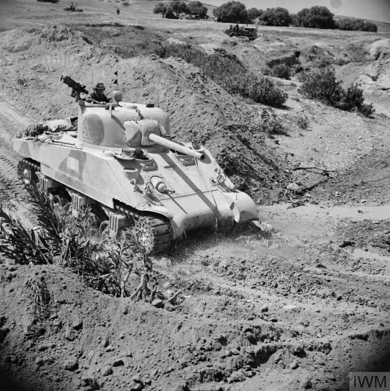 A Sherman tank crossing a wadi, 22 Apr 1943. IWM photo NA 2359.