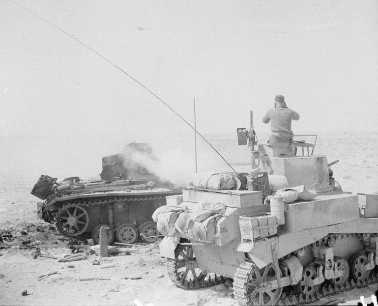 The commander of a Stuart tank uses a knocked-out PzKpfw III tank as cover while observing the enemy, 1 Jun 1942. IWM photo E 12670.