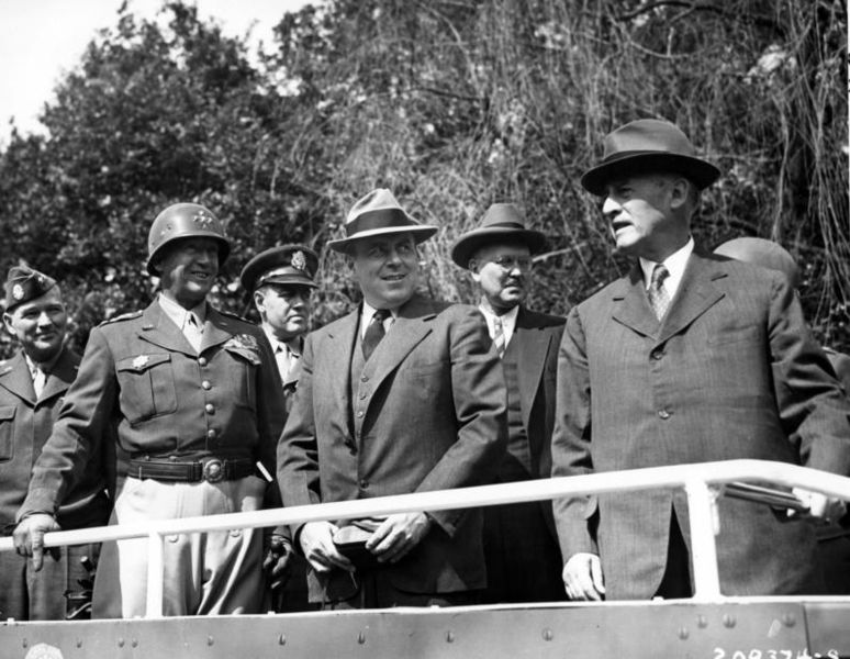 From left to right: Major General Floyd Parks, U. S. Commanding General, Berlin Area; General George S. Patton, Jr., Commanding General, U. S. 3rd Army; Colonel William H. Kyle, aide to Secretary of War Stimson; John J. McCloy, Assistant Secretary of War; Harvey H. Bundy; and Secretary of War, Henry L. Stimson stand in a half track as they review the 2nd Armored Division, in Berlin, Germany during the Potsdam Conference. 20 Jul 1945. U.S. Army photo