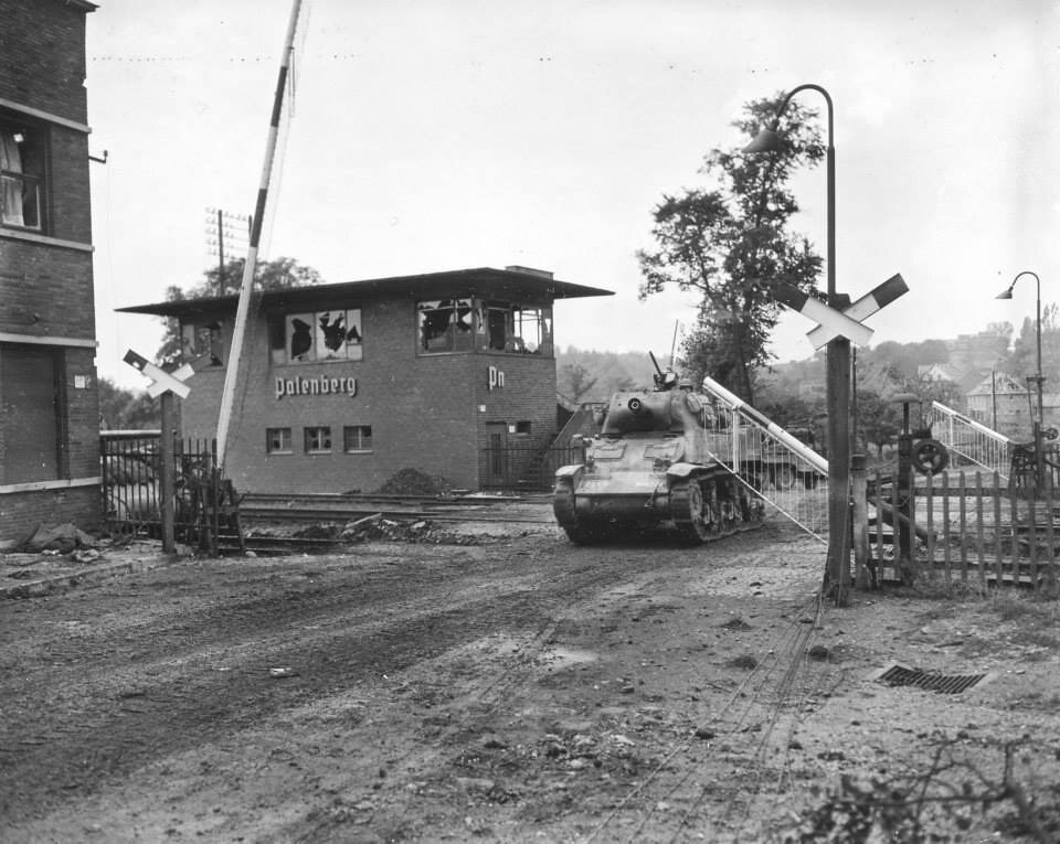 2AD M8 Howitzer Motor Carriage crossing the railway line at Palenberg, Germany, Oct 1944