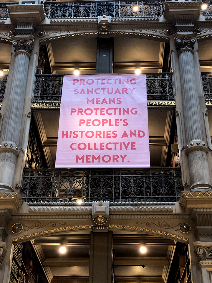 Pink banner at the George Peabody banner that reads: Protecting sanctuary means protecting people's histories and collective memory.