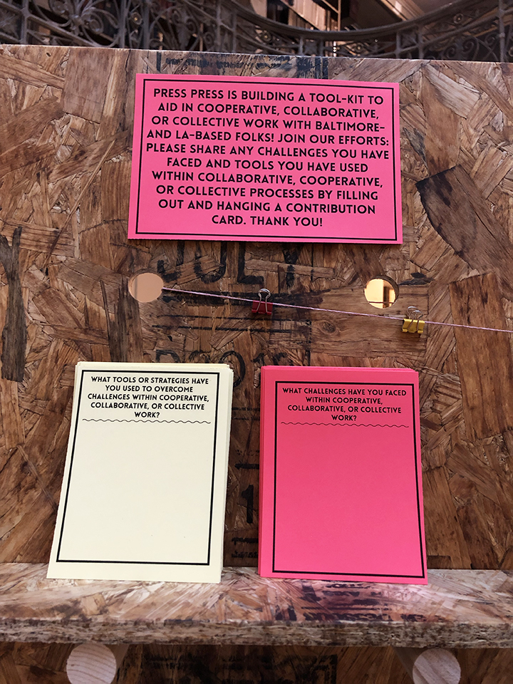 Display stand with text on magenta paper that asks visitors to fill out comment cards on the challenges of collaborative work and useful strategies