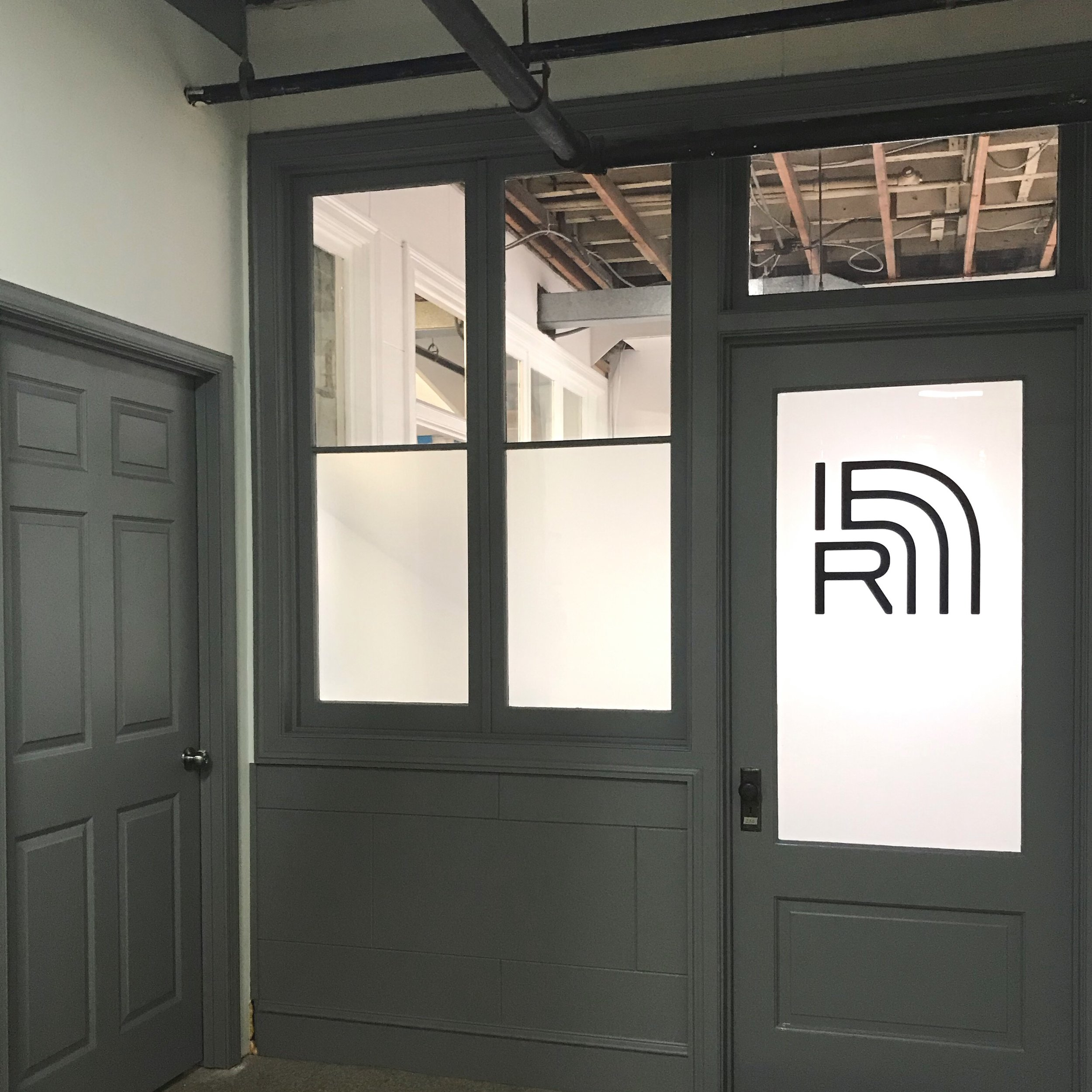 Photo of Institute for Expanded Research studio showing a gray storefront with frosted windows and the IER logo.