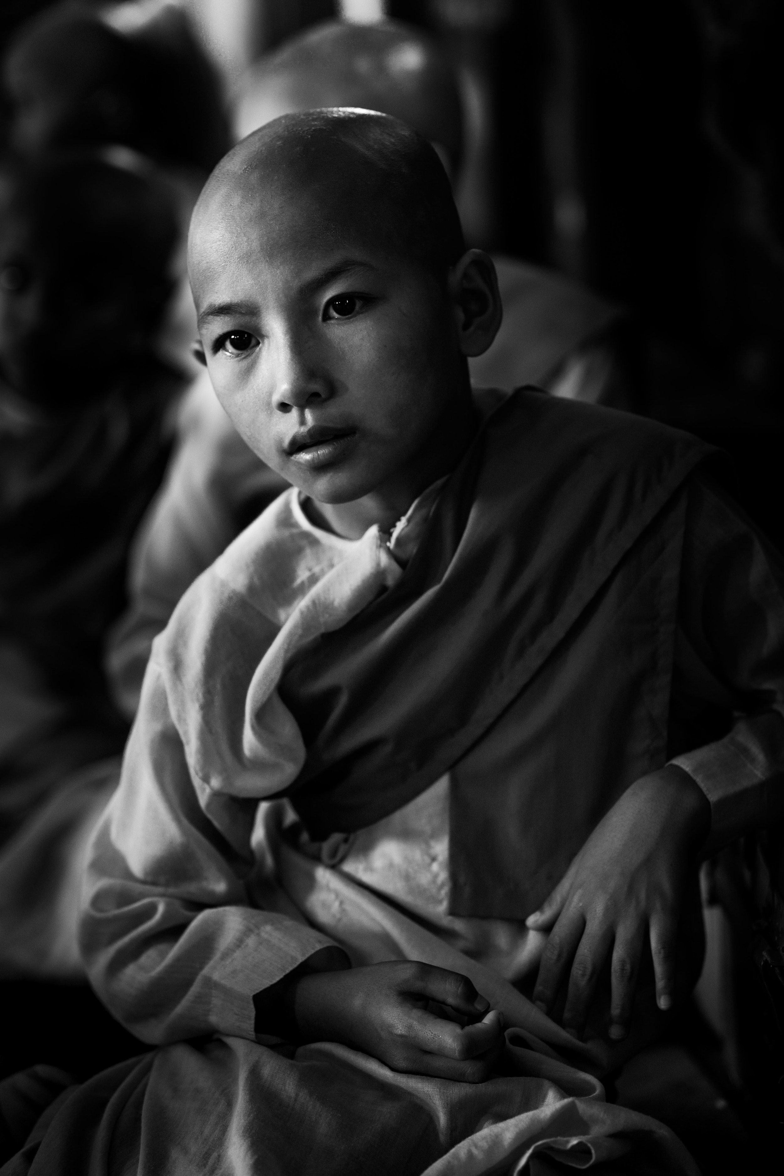 Novice nun sits during an Assembly from the series Portraits of Myanmar.