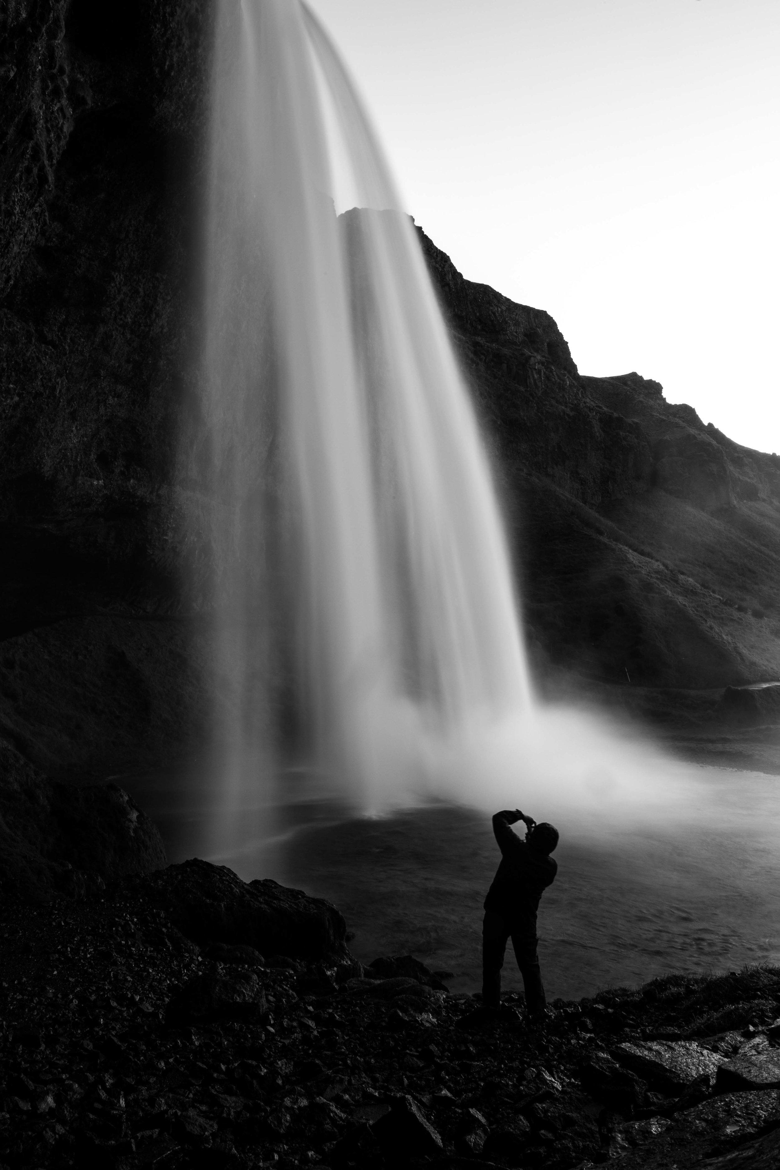 A man photographs Seljlandsfoss, a waterfall - Iceland