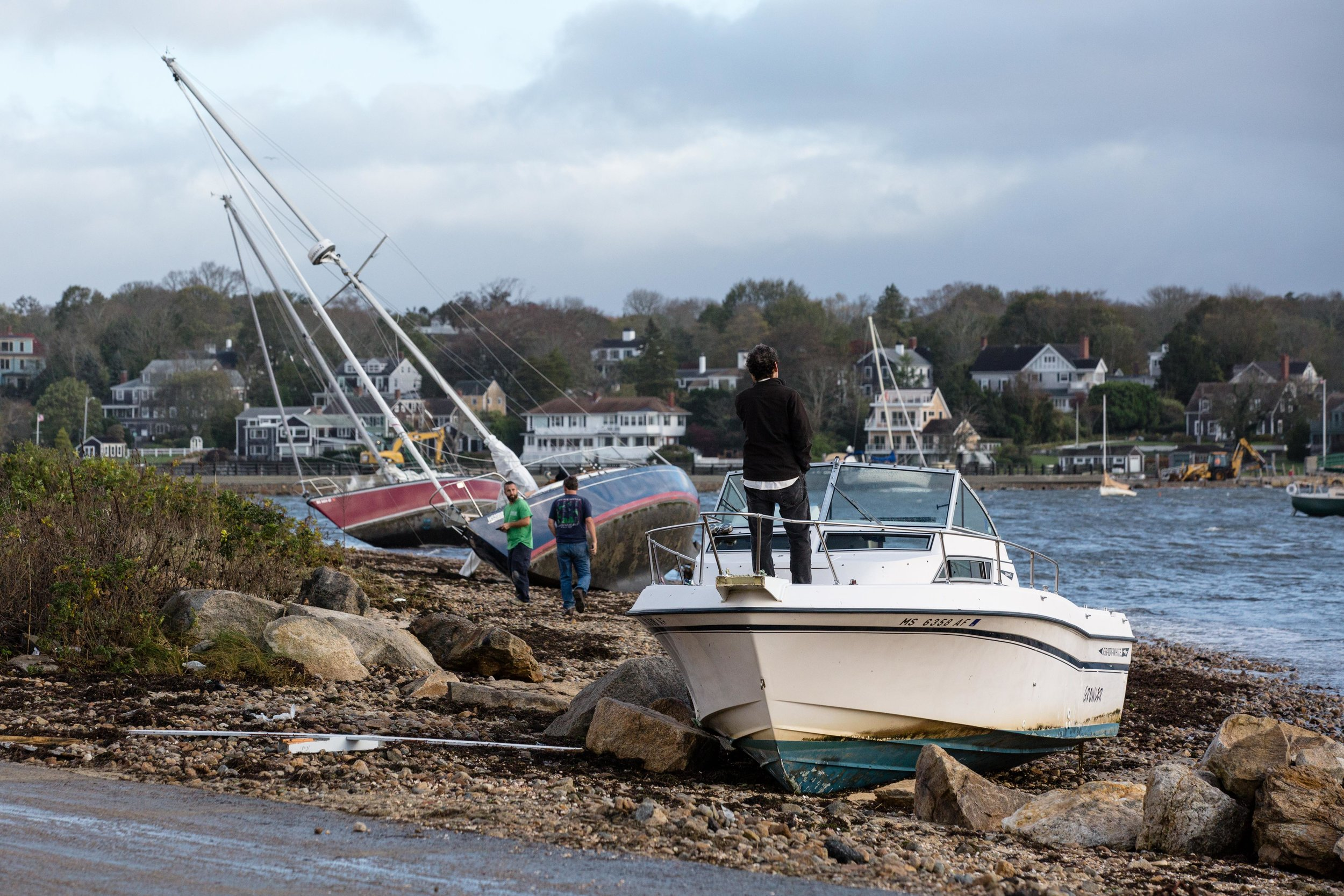 A man stands on the bow of his beached powerboat.