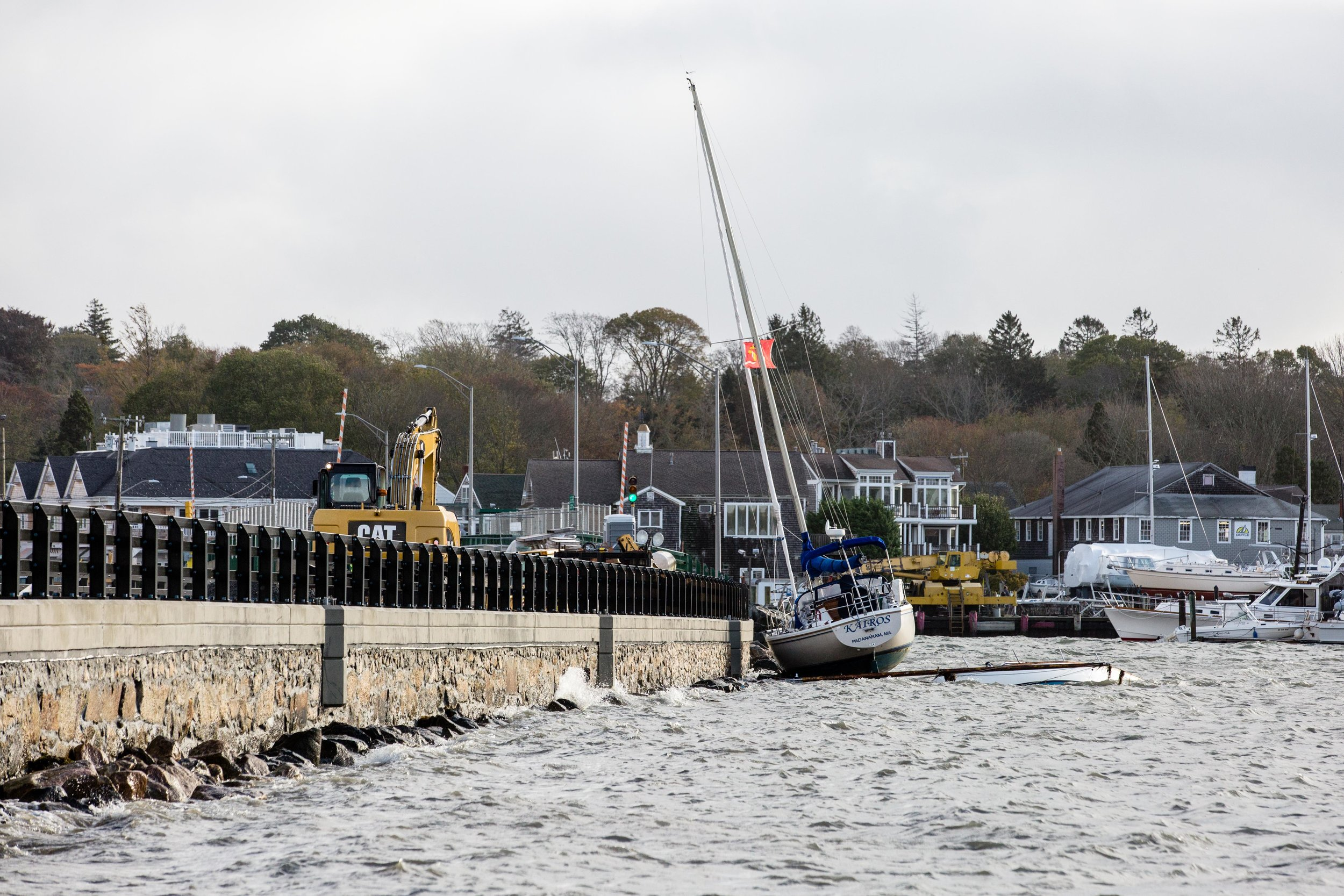 A sailboat gets stuck against the causeway while a capsized powerboat lies beneath it.