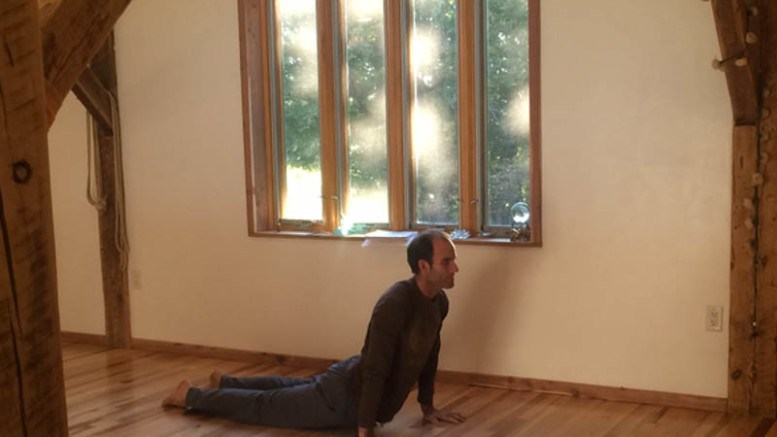 Christopher Grant, owner of Yoga Farm, demonstrates a pose for a yoga class.