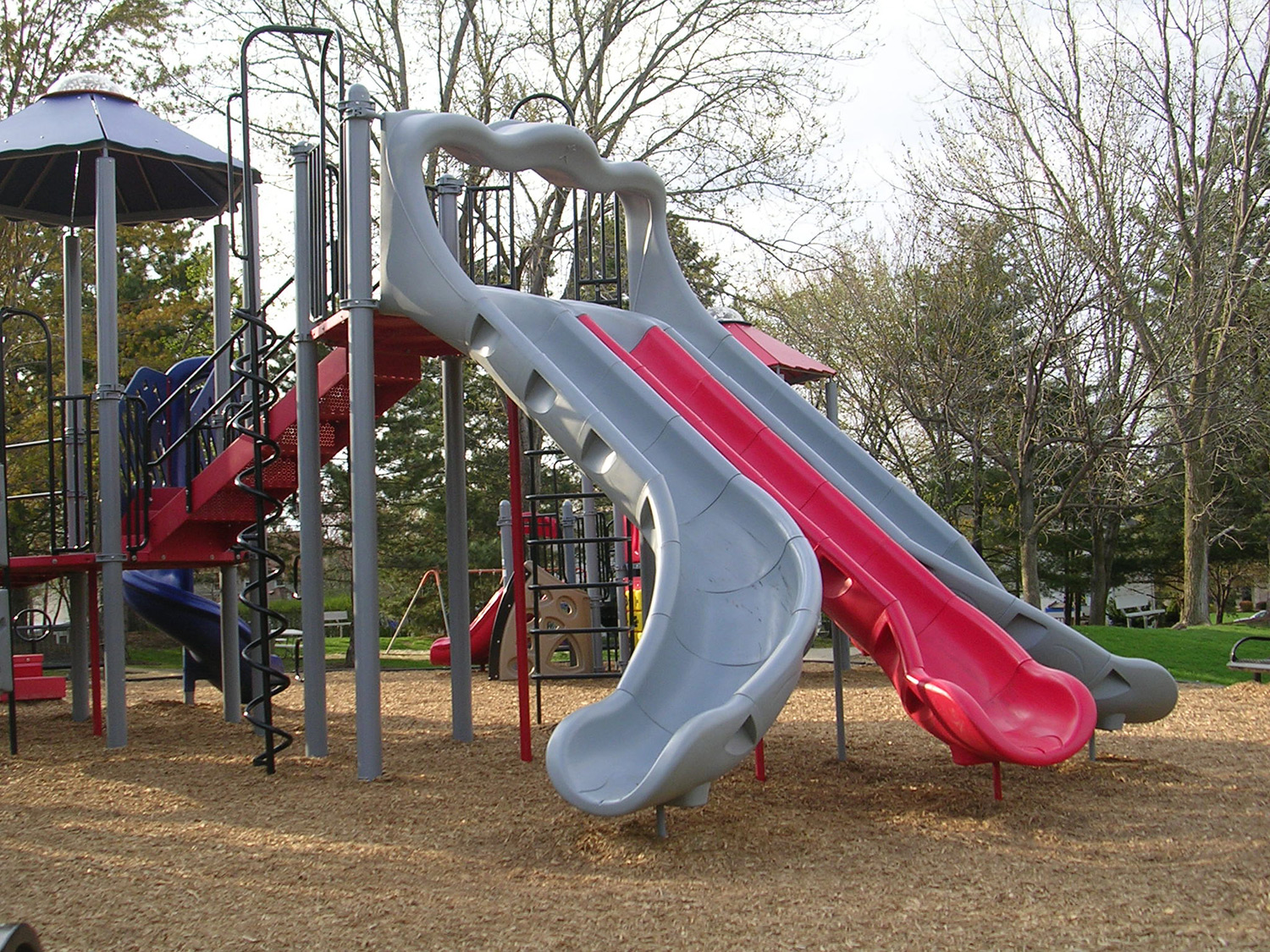 Situated with nearby trees, the playground also includes several sets of swings.